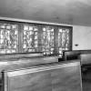 Cappella di bordo, visibili le Acquasantiere e la Fonte battesimale; la vetrata è di Dino Predonzani